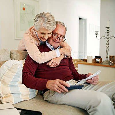 Buy stock photo Shot of a senior woman embracing her husband while he works out their monthly budget