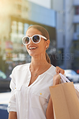 Buy stock photo Shot of a happy young woman on a shopping spree in the city
