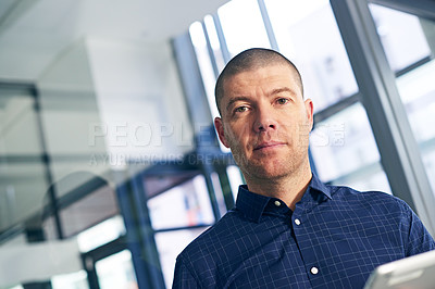 Buy stock photo Portrait of a businessman using a digital tablet in a modern office