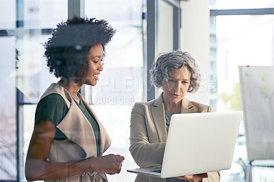 Buy stock photo Shot of two colleagues discussing something on a laptop