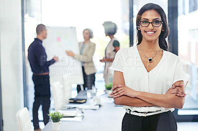 Buy stock photo Portrait of a businesswoman standing in an office with her colleagues in the background