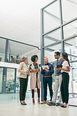 Buy stock photo Shot of a group of colleagues having an informal meeting in an office