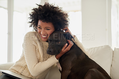 Buy stock photo Shot of an attractive young woman petting her dog while sitting on the sofa at home