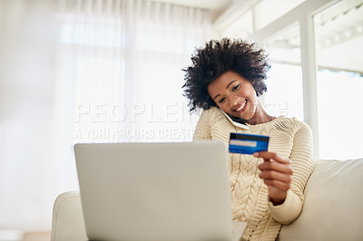 Buy stock photo Shot of an attractive young woman shopping online using her laptop while sitting on the sofa at home