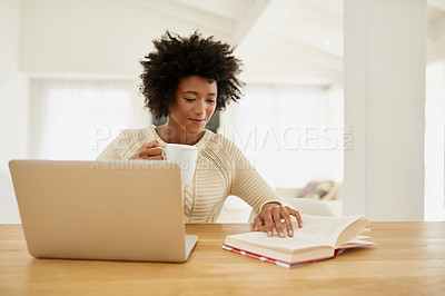 Buy stock photo Shot of an attractive young using her laptop, reading a book and drinking some coffee at home