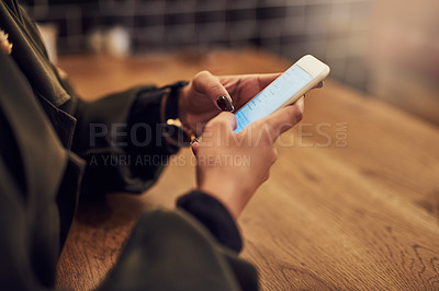 Buy stock photo Cropped shot of a woman using her cellphone in a cafe
