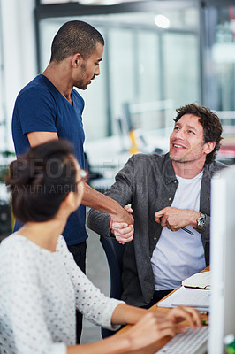 Buy stock photo Shot of a group of designers talking together while sitting at their workstations in an office
