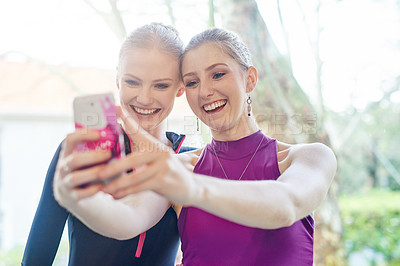 Buy stock photo Cropped shot of two sporty young women taking a selfie after their workout