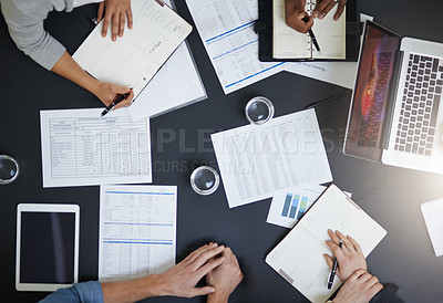 Buy stock photo Cropped shot of a team of colleagues going through paperwork during a meeting at work