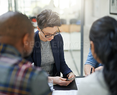 Buy stock photo Shot of a businesswoman using her phone during a business meeting