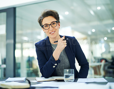 Buy stock photo Portrait of a happy businesswoman working at her desk in a modern office