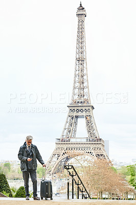 Buy stock photo Shot of a mature man with a suitcase using a cellphone in Paris with the Eiffel Tower in the background