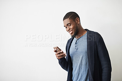 Buy stock photo Studio shot of a young man using a cellphone against a gray background