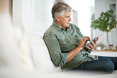 Buy stock photo Cropped shot of a mature man using a digital tablet at home