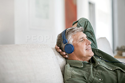 Buy stock photo Cropped shot of a mature man listening to music with headphones on at home