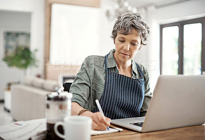Buy stock photo Shot of a mature woman making notes while working on her laptop at home