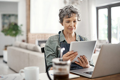 Buy stock photo Shot of a mature woman using her tablet while working on her laptop at home