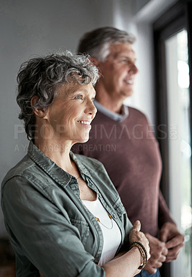 Buy stock photo Shot of a mature couple looking out the window