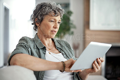 Buy stock photo Shot of a mature woman using her tablet while sitting on the sofa at home