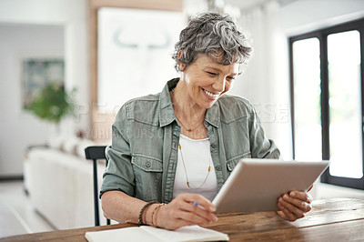 Buy stock photo Shot of a mature woman using her tablet at home