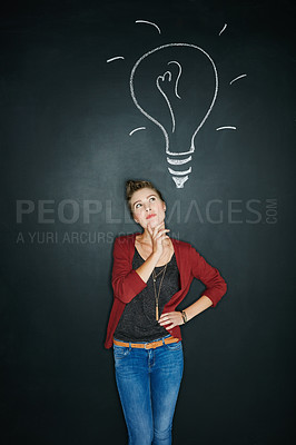 Buy stock photo Studio shot of a young woman posing with a chalk illustration of a lightbulb against a dark background