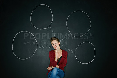 Buy stock photo Studio shot of a young woman posing with a chalk illustration of thought bubbles against a dark background