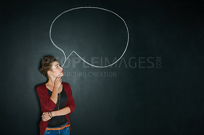 Buy stock photo Studio shot of a young woman posing with a chalk illustration of a speech bubble against a dark background