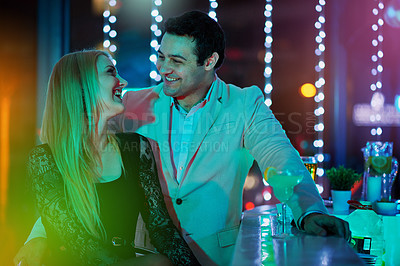 Buy stock photo Shot of two young people chatting at a bar