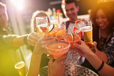 Buy stock photo Shot of a group of people toasting with their drinks at a nightclub