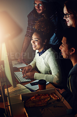 Buy stock photo Shot of a business team looking at a computer screen together on a night shift at work