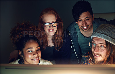 Buy stock photo Shot of a business team looking at a computer screen on a night shift at the office