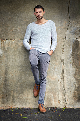 Buy stock photo Shot of a handsome young man posing against an urban wall