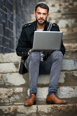 Buy stock photo Shot of a handsome young man sitting on urban steps and using a laptop