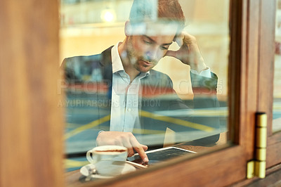 Buy stock photo Shot of a young businessman using his tablet while sitting in a coffee shop