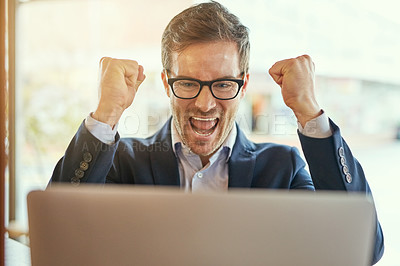 Buy stock photo Shot of a young businessman cheering while using his laptop while sitting in a coffee shop