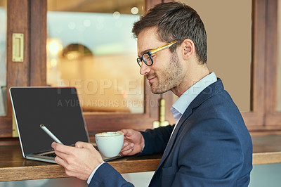 Buy stock photo Shot of a young businessman sending a text message while sitting in a coffee shop