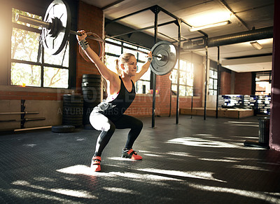 Buy stock photo Shot of a young woman working out with a barbell at a gym