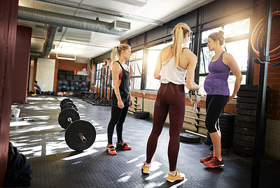 Buy stock photo Shot of a group of young women having a discussion at the gym