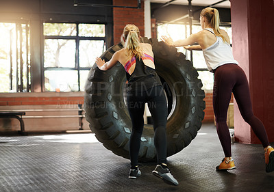 Buy stock photo Shot of two young women doing doing a tire flip at a gym