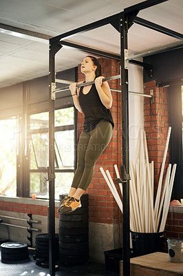 Buy stock photo Shot of a young woman doing chin ups at a gym