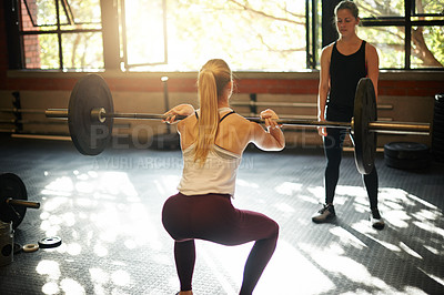 Buy stock photo Rearview shot of a young woman working out with a barbell at a gym