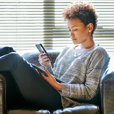 Buy stock photo Cropped shot of a young woman using a cellphone and digital tablet at home