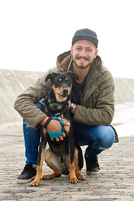 Buy stock photo Portrait of a young man and his dog spending time together outdoors