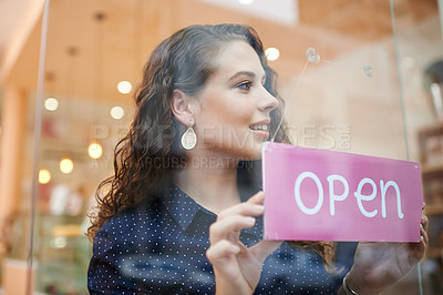 Buy stock photo Shot of a young woman hanging an