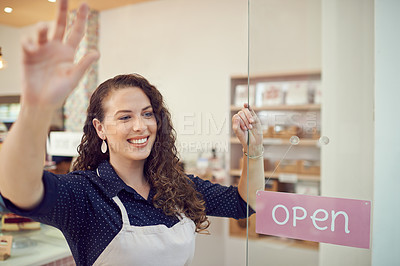 Buy stock photo Shot of a young woman waving from the door of her cake shop