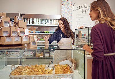 Buy stock photo Shot of a young woman helping a customer in her cake shop