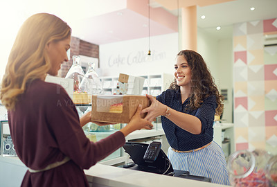 Buy stock photo Shot of a young woman handing a box to a customer in her cake shop