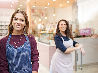Buy stock photo Portrait of two young entrepreneurs standing by the door of their cake shop