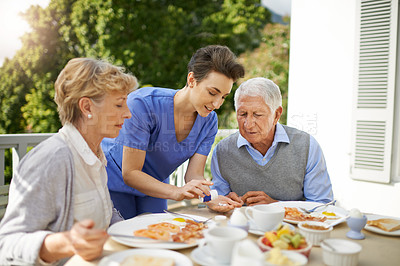 Buy stock photo Shot of a nurse assisting a senior couple at breakfast