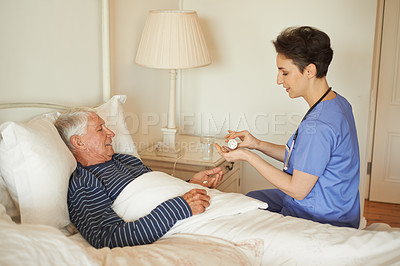 Buy stock photo Cropped shot of a female carer assisting her patient with his medication in a nursing home
